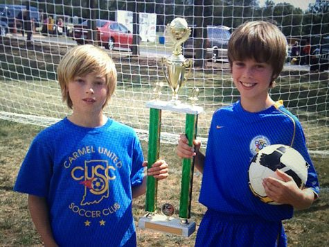 """(TOP) Junior Cam Adams (left) poses with a trophy with his brother and senior Harrison Adams when they were 10 and 11 years old, respectively. This year, the Adams brothers played together for the first time. Harrison said, """"We have a lot of fun together, we get to joke around, just mess around doing what brothers do, and playing on the same team as well."""""""