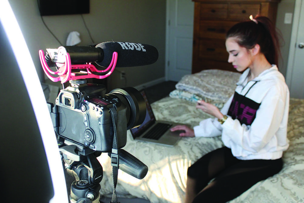 """Shelton sits on her bed with her camera and microphone set up to take audio and video. Of her equipment, Shelton said, """"Once you have a nice set-up, it just makes your videos look and feel a lot better."""""""