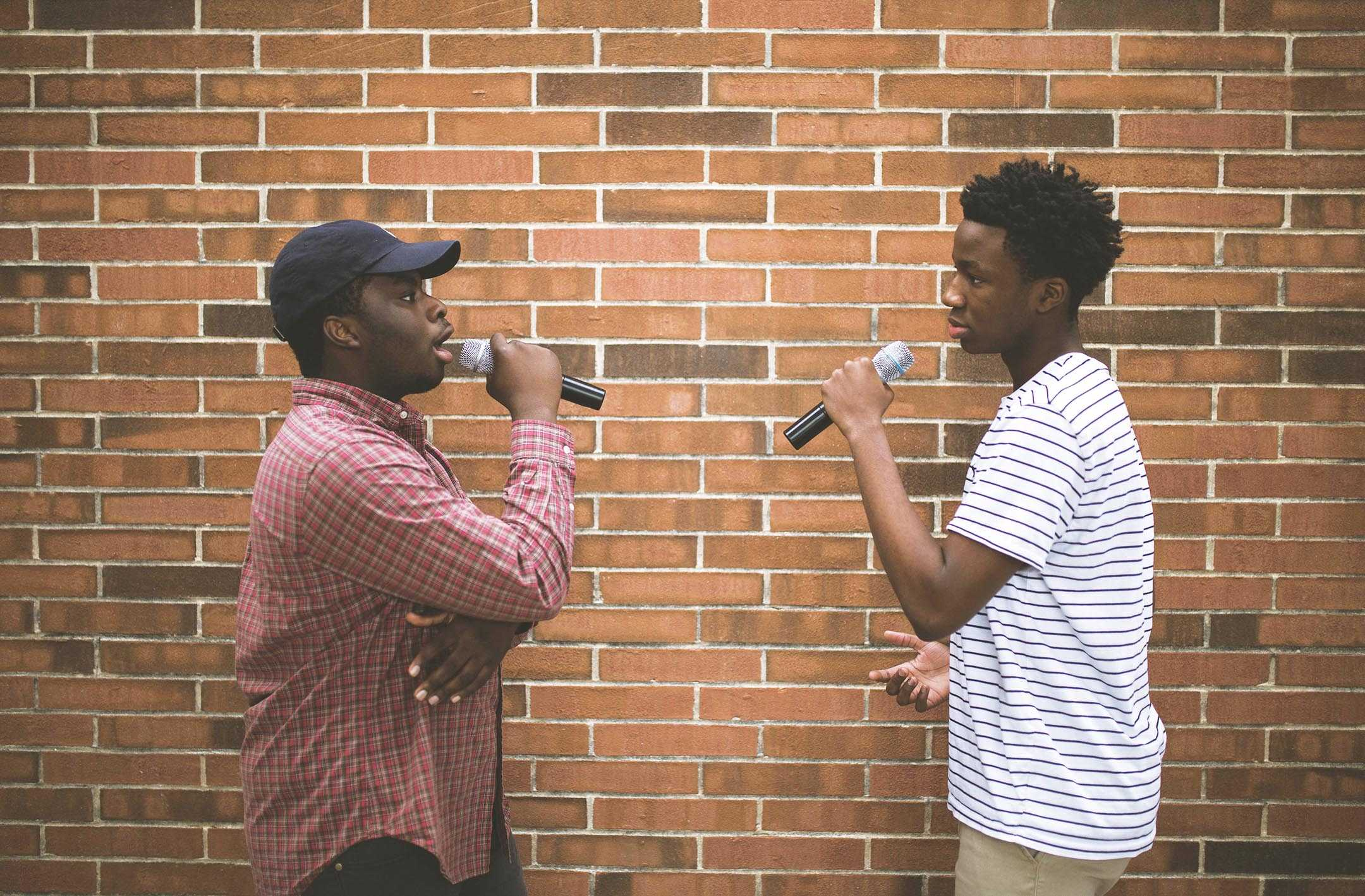 "FANCY FLOW: Rappers and juniors David Chilemba and Rashid ""RJ"" Conteh face each other holding microphones. Conteh said the duo drew inspiration from rapper Kanye West."