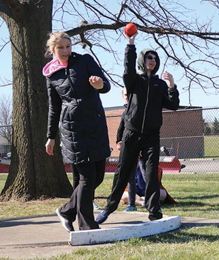 Coach and senior Mallory Davis helps senior Noah Sachs with the shot put event. Unified Track is an IHSAA-sanctioned sport.