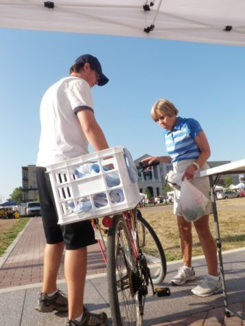Andrew Smith, CMYC member and junior, returns a bike to a Farmers' Market visitor who used the services provided by Park My Ride. As one of services provided by CMYC, Park My Ride is a free bike parking service hosted every Saturday from 8 to 11 a.m. for anyone visiting the Farmers' Market.