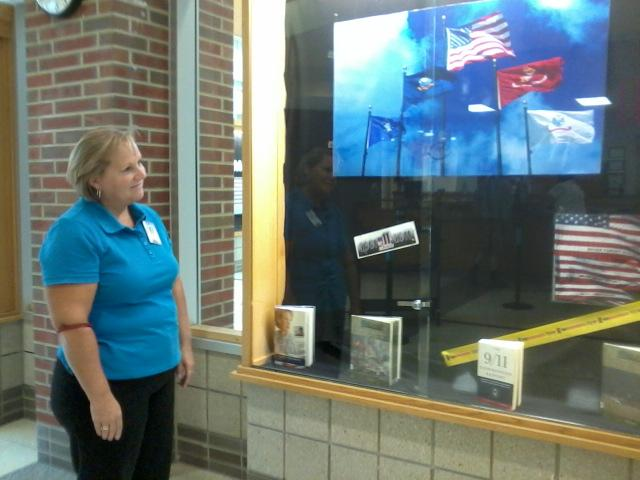 Media manager Michelle Martin gazes at the 9/11 display that she worked on. Martin filled the 9/11 display with various books on 9/11, memorabilia and handmade posters. The media center worked with AVID students to display a series of exhibitions commemorating 9/11. DAVID CHOE / PHOTO