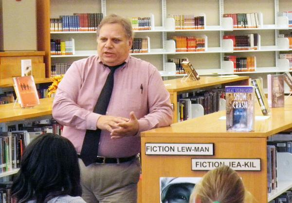 Media specialist John Shearin shares a book with students during a class visit to the media center. Shearin said that the media staff will add new technology to enhance the media center experience for students. DAVID CHOE / PHOTO