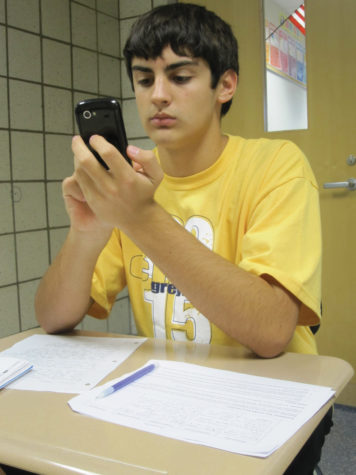 Freshman Colby Cronnin checks his smartphone while doing homework. Cronnin said he has started obsessively checking his cell phone, even while he is studying. KATHLEEN BERTSCH / PHOTO
