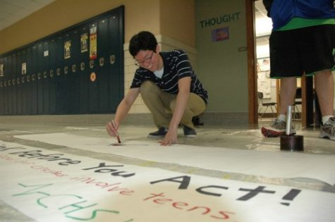 Chris Song, LifeLines member and senior, decorates a poster advertising Red Ribbon Week. This event is week-long campaign to raise awareness of the dangers of drugs and violence. ARUNI RANAWEERA/ PHOTO