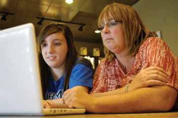 """STUDENT BECOMES THE TEACHER: Junior Dana James teaches her mother some basic actions on Facebook. """"Basically,"""" said James, """"I just have to show Mom the ropes, and occasionally, I have to show her something new, but otherwise, she's a fast learner. She knows her way around the site."""" GAVIN COLAVITO / PHOTO"""