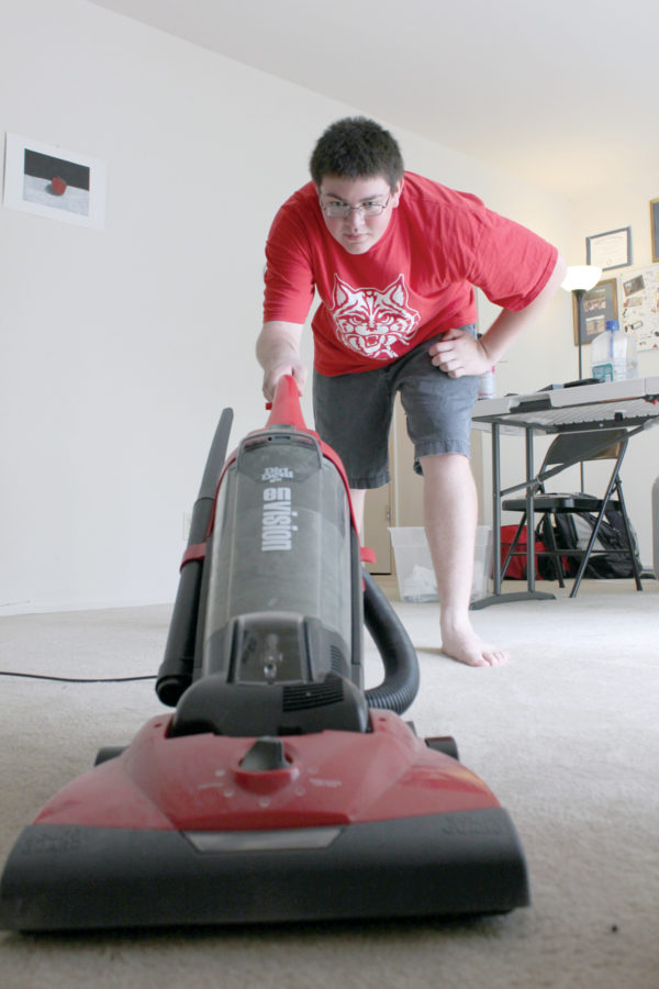 HOME ALONE: Senior Frank Molina cleans his apartment. After he became emancipated, Molina said he has taken on responsibilities usually reserved for adults. HENRY ZHU / PHOTO