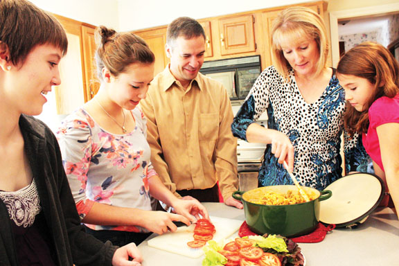 """Cultural kitchen: The Arroyo family makes """"arroz con gandules,"""" which is a traditional Puerto Rican dish consisting of green bell peppers, onions, tomatoes, rice and pigeon peas. The family enjoyed making different cultural foods from both sides of the family. PHOTO / MIKAELA GEORGE"""