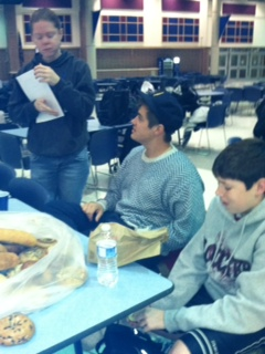 Student Venture leader Carolyn Wiley passes out surveys to junior Kevin Krauter and sophomore Tyler Meinz during the Jan. 10 meeting. According to Kate Shanklin, S.A.L.T. member and senior, the survey was about how students incorporated their faith into New Year's resolutions.