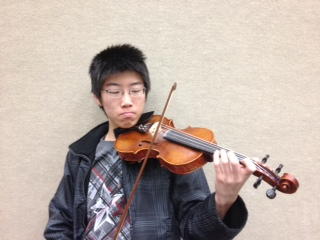 Sen Xiong, orchestra member and junior, practices for the ISSMA state competition. According to Xiong, the orchestra's good performance at districts assured that they would qualify for state. RYAN ZUKERMAN / PHOTO