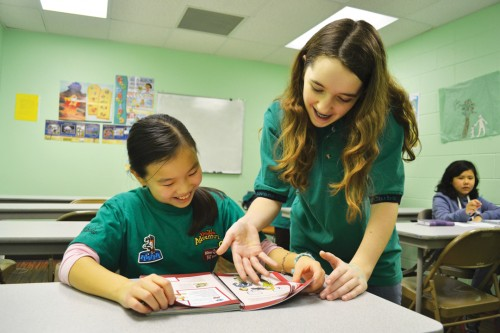 Freshman Kinsey Erickson reviews a Bible story with a student at the Chinese Community Church of Indianapolis. Erickson said she experiences sleep debt due to her extra-curricular activities.