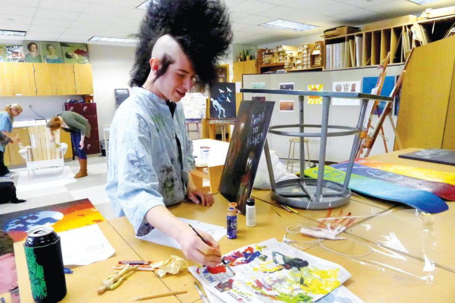 """ART SMART: Senior Nathaniel """"Nate"""" Harcourt works on an art piece during AP Studio Art. According to Harcourt, his portfolio deals with how media twists society. OMEED MALEKMARZBAN / PHOTO"""