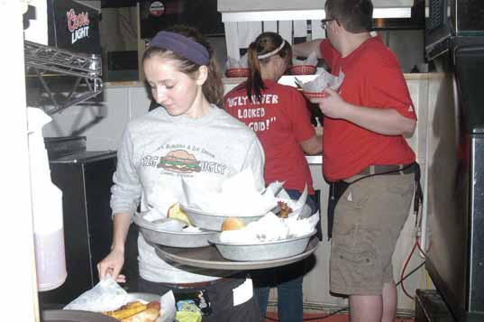 Stacking Up: Junior Rachel White gathers dishes of food to serve to her customers at Bub's Burgers and Ice Cream. White, who has been a waitress at the restaurant for three years, said she has learned how to apply her personality to different kinds of customers. Hailey Meyer / Photo