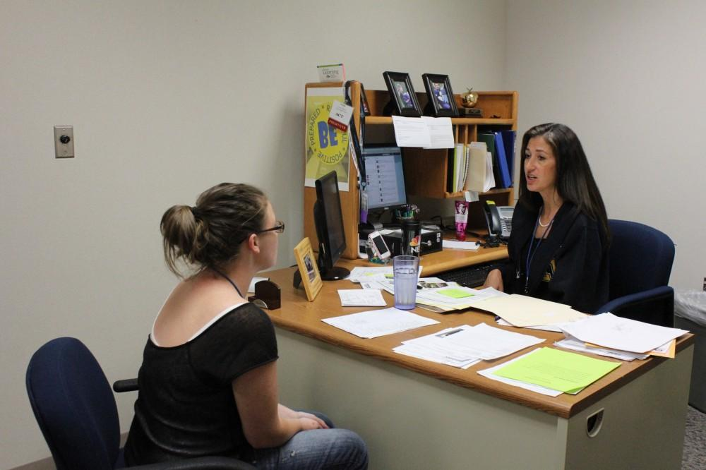 Newly hired college coordinator Linda Christy speaks with senior Michaela Carpenter about her college options.