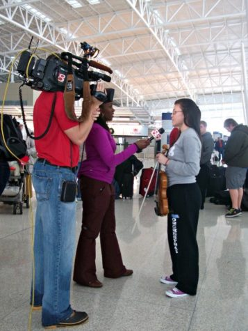 A WishTV reporter interviews Melinda Song, symphony orchestra member and senior, at the Indianapolis International Airport. The orchestra was planning to travel to China for a group trip but had their flight postponed due to weather. Local news stations interviewed the orchestra on their situation. ROCHELLE BRUAL/ PHOTO