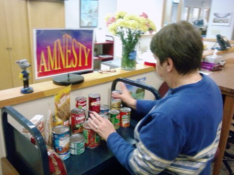 Media manager Donna Prather sorts through the donated cans for the