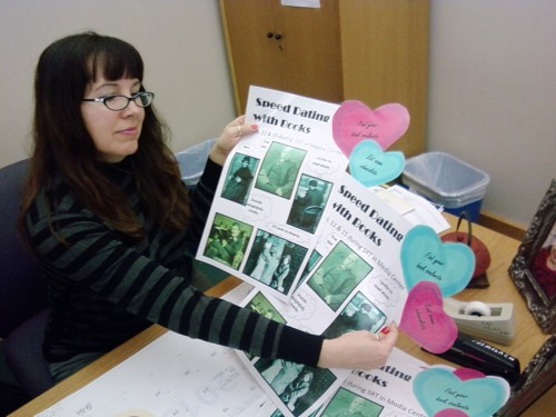 Media manager Shanna Mooney displays working posters promoting the
