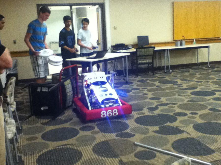 Sophomore Aryaman Gupta and other TechHounds member test out an old robot.  TechHounds is preparing for a Cage Match in October, where they will scrimmage with last year's robot at Southport High School.