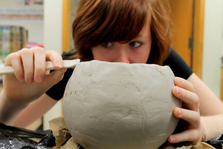 Freshman Gracie Coleman crafts the edge of a clay pot. Coleman said she expects far less cheating in her ceramics class, especially when compared to her more traditional classes. NIVEDHA MEYYAPPAN / PHOTO