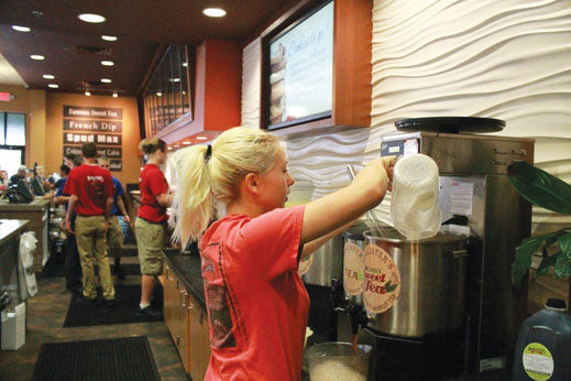 Kristina Pitchkites, McAlister's Deli employee and junior, mixes sweet tea for customers at the Tea Bar. She said she decided to get a job in order to pay for college and gas. MILES DAI / PHOTO