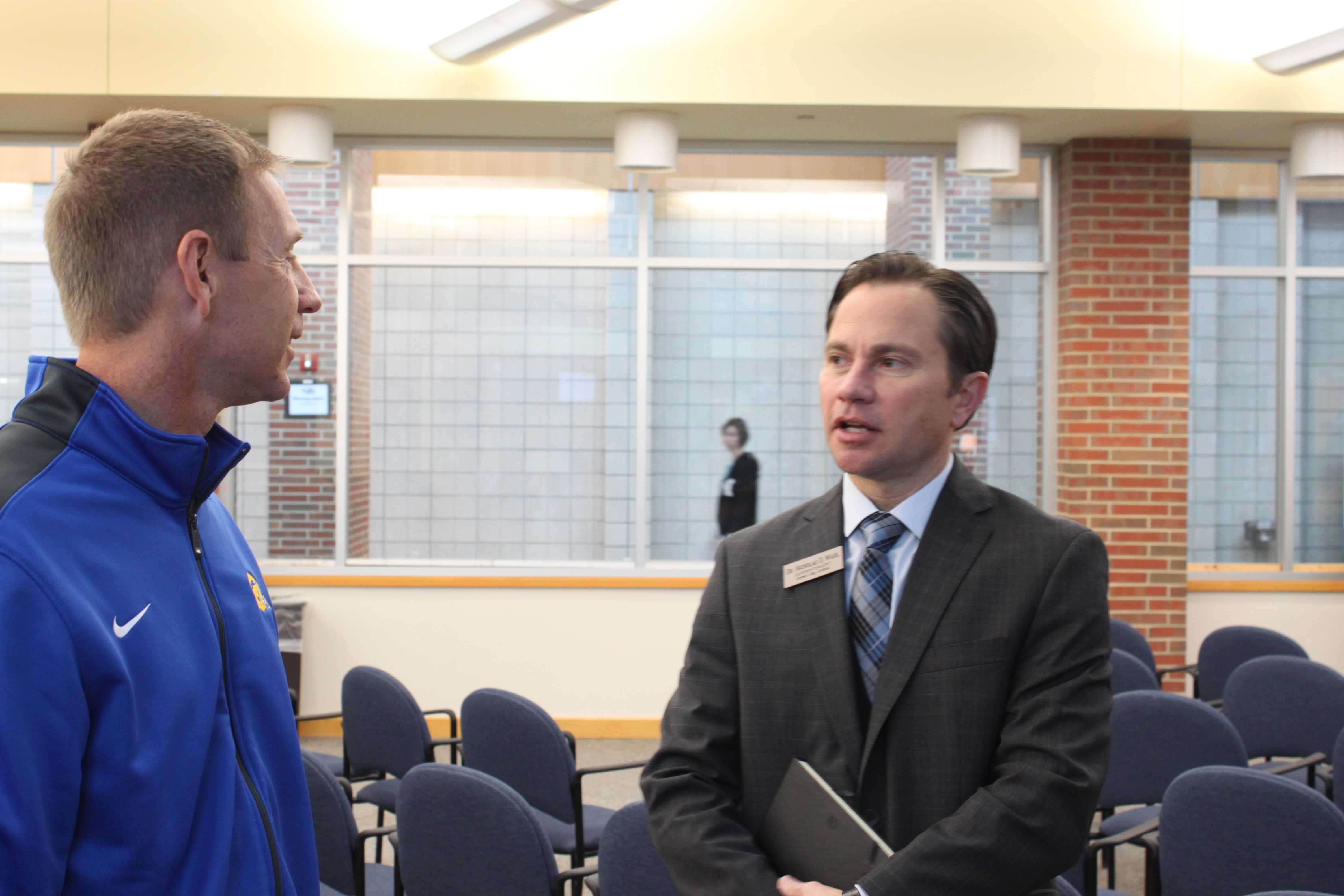 Superintendent Nicholas Wahl speaks to Kevin Wright, head coach of the football team, after a teacher award ceremony that took place on Nov. 1. Wahl said he hopes to increase communication with teachers, parents and students across the district. JOSEPH LEE / PHOTO