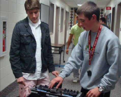 Senior Samuel Pickett (left) instructs another WHJE staff member on using a portable sound system. Along with being a member of WHJE, he is also successful academically.