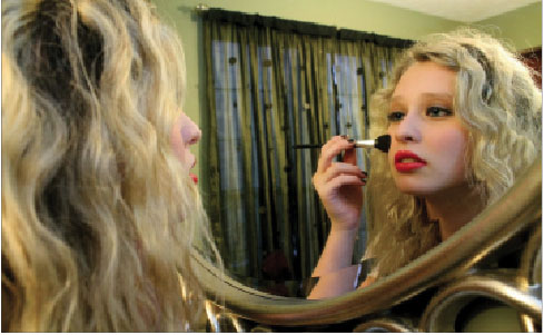 """Junior Eva Bublick applies foundation in front of her mirror. Bublick said, """"Everyone should feel pretty and for some people, makeup makes them feel pretty."""""""
