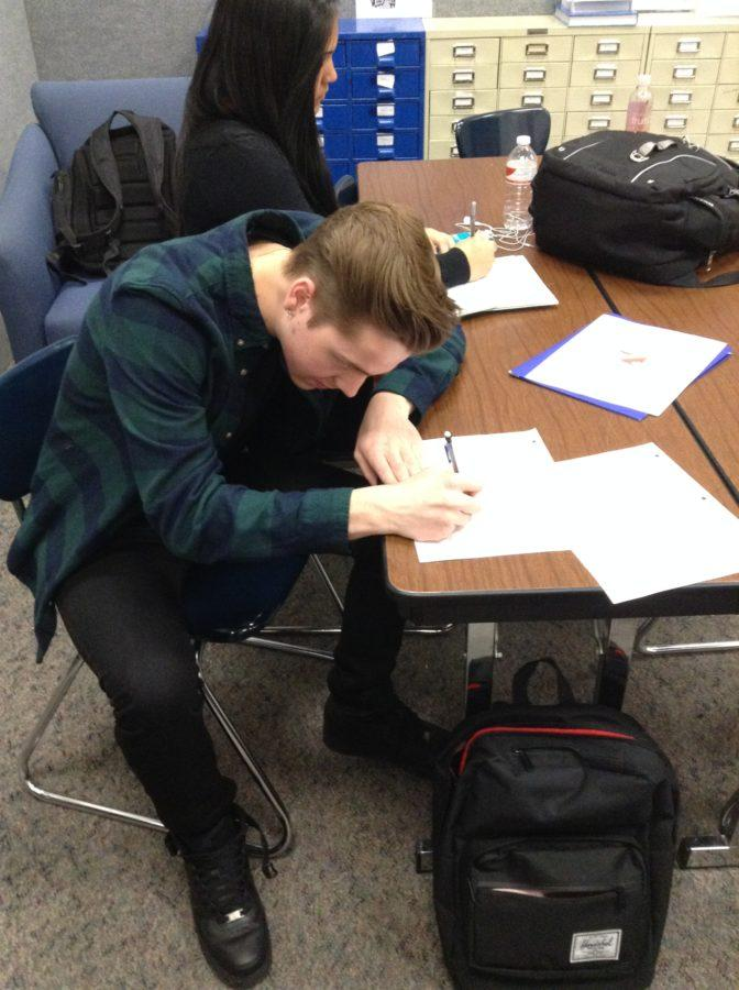 """Brad Davis, CHTV member and senior, works on sports announcements and writes out outlines during a CHTV SRT on Jan. 21. """"What do I do for CHTV? What do I not do,"""" Davis said. """"CHTV makes me happy inside. NATALIA CHAUDHRY / PHOYO"""
