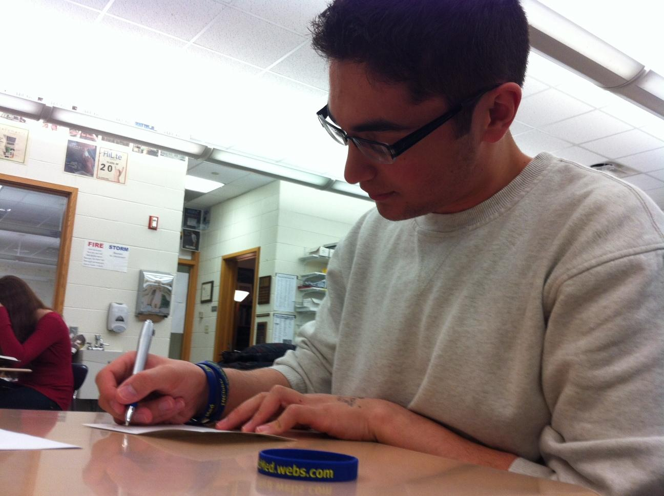 Omeed Malek, Club Med president and senior, writes a note for a teacher. He said he would discuss volunteer opportunities at the next meeting, especially opportunities at St. Vincent Hospital. AARON SHI / PHOTO