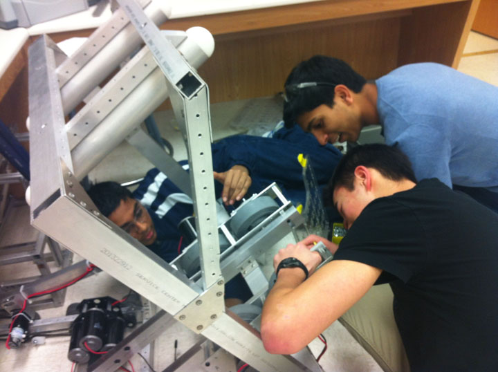 Sophomores Sameer Leley, Aryaman Gupta and Kalen Rudd make adjustments to the shooter. TechHOUNDs tested out its prototype for the first time after school on Monday, Jan. 27. PHOTO / JESSICA TAO