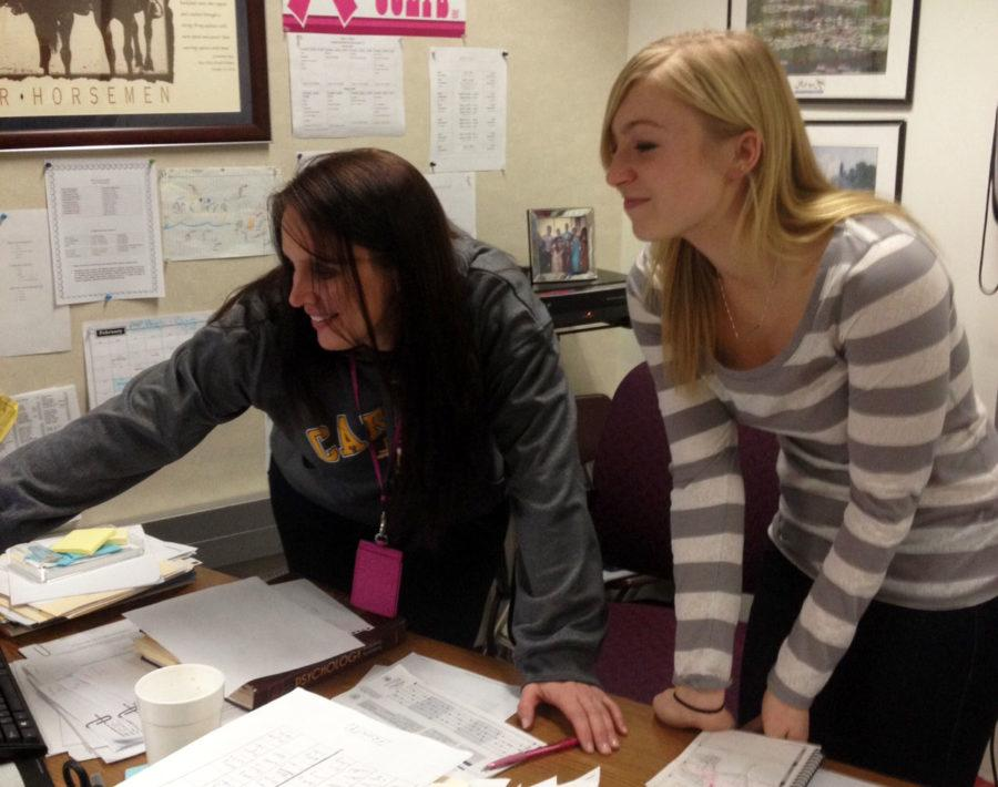 K-8 Mentoring sponsor Robin Pletcher and mentor and senior Carly Sieber look over a document for K-8 Mentoring. The mentors have had to adjust to the missed school and are looking forward to fulfilling the requirement of four outings per nine weeks. LUCUS CHENG / PHOTO