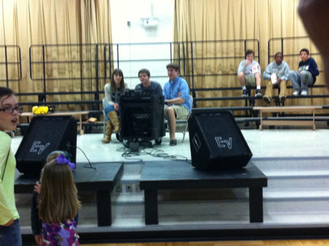 At Towne Meadow Elementary, some WHJE students deejay for young kids in a gymnasium. At the program, students played songs such as