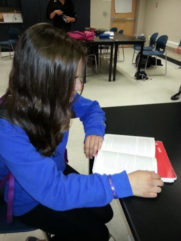 Lilly St. Angelo reads a book in her English class. St. Angelo had a CRU meeting that morning, and she said she had a good time. ANUJ PATEL / PHOTO