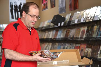 The Foolery owner Bob Williams looks at his most classic comic books. Williams reopened the Foolery, a comic book store in downtown Carmel.