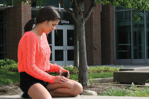 Sophomore Sophie Page sprays tanning oil onto her legs before tanning. Page said she has used a tanning bed before, but still supports the recent ban on the use of tanning beds for minors under the age of 16. SARAH LIU / PHOTO