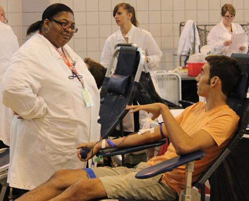 Chatting casually with a nurse, Nicholas Dunbar 14 gives blood in the fall blood drive of 2012. This years drive will take place on Sept. 5. SCOTT LIU / PHOTO