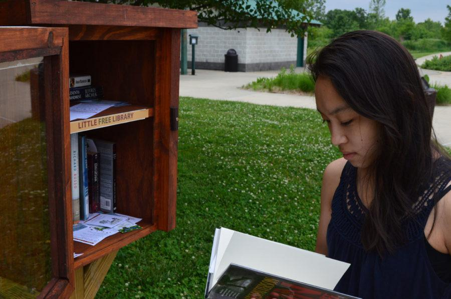 Sarah Tinaphong, House of Books co-president and junior, examines a book from a Free Little Library at West Park. Tinaphong said these libraries serve as a convenient source of new books. ALEX YOM / PHOTO