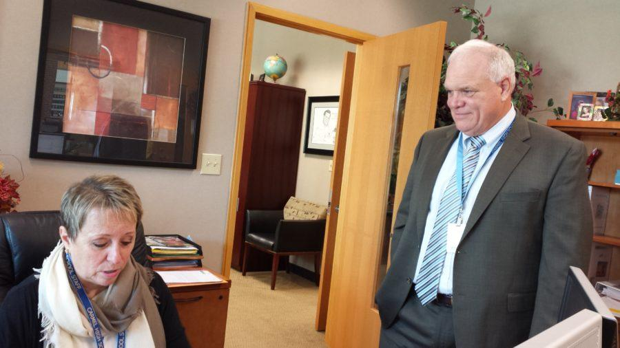 Principal John Williams talks to secretary Jan Brown.  This year on Oct. 15, seniors will attend panels of college representatives while other grades take the PLAN and PSAT. HELENA MA/PHOTO