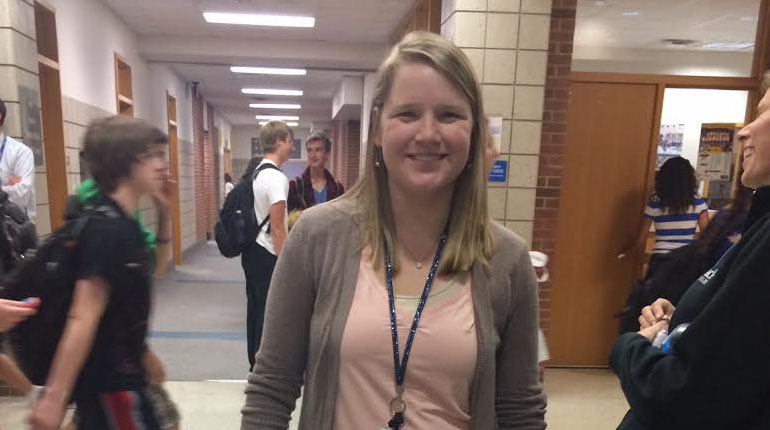 Pinnacle adviser Nicole Laughrey smiles near the entrance to the communications department. She said everyone who purchased a yearbook will receive the supplement as well.