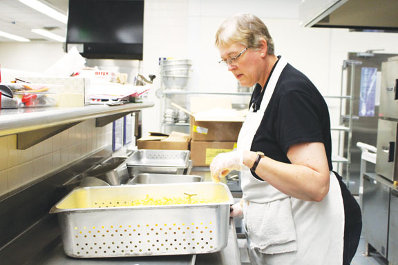 Cafeteria worker prepares food that adheres to new nutrition requirements. SARAH LIU / PHOTO