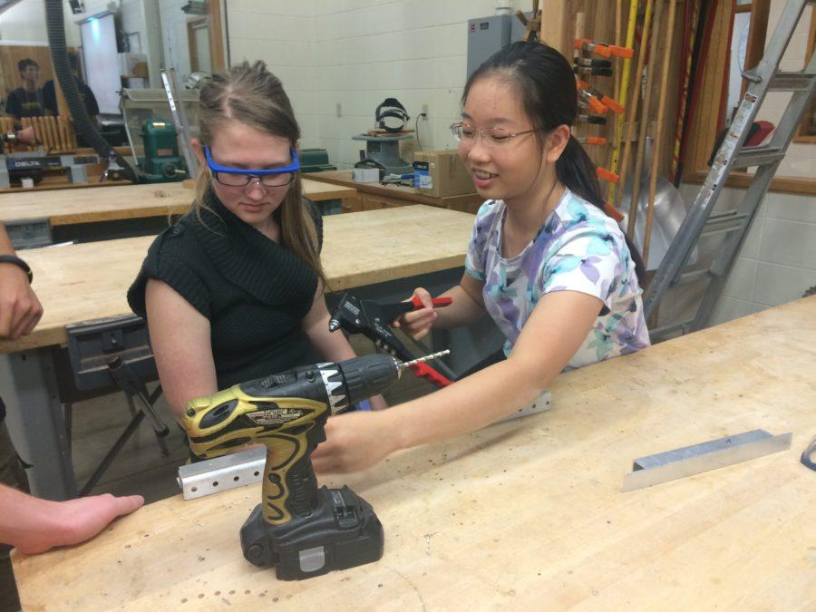 TechHOUNDS member and junior Cynthia Chang uses a rivet gun to join two pieces of aluminum together. Veteran members are training new members how to use different tools so the members will be better prepared for build season. JESSICA TAO/PHOTO