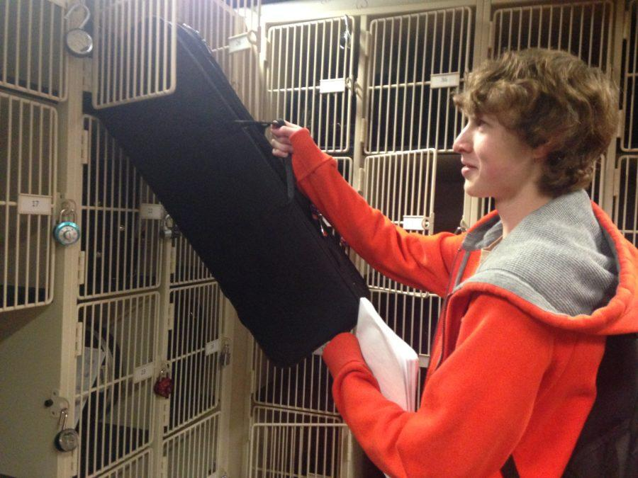 James Adams, Philharmonic Orchestra member and senior, puts away his violin into his orchestra locker after school. Adams said he does a lot of practicing during his orchestra independent study period. MICHELLE DAI / PHOTO