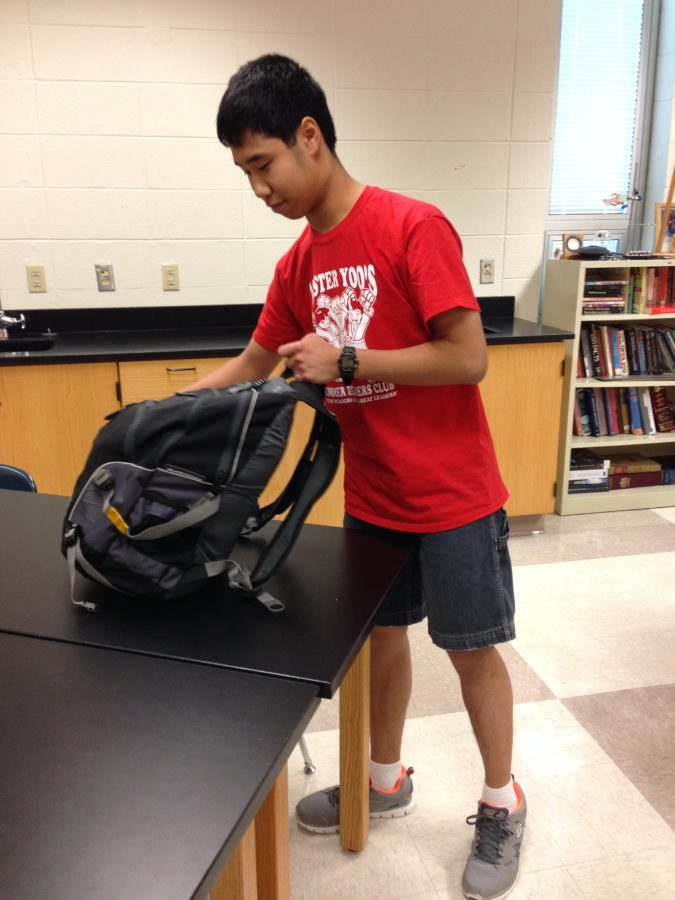 Ryan Jou, Chemistry Club president and junior, gets textbooks out of his backpack. According to Jou, the club plans to make magic sand at the next meeting.