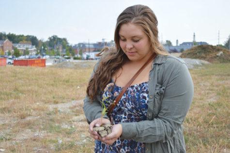 Elizabeth Baach, Carmel Green Initiative board member and junior, plants a plant near the construction. Baach said she opposes the Monon Lake construction plan due to its environmental impact. ALEX YOM / PHOTO
