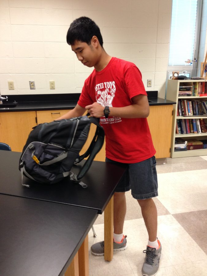 Ryan Jou, Chemistry Club president and junior, gets textbooks out of his backpack. According to Jou, the club plans to conduct demonstrations at the next meeting.