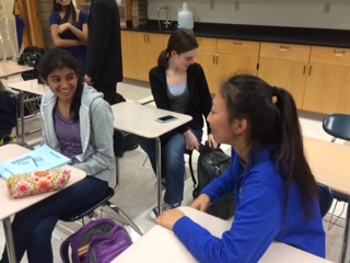 Junior Gloria Xue talks to her friend before class. Xue said that it would be worthwhile to attend the Youth Changing the World event.