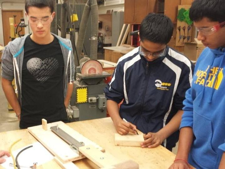 Juniors Kalen Rudd, Aryaman Gupta and Sameer Leley fix the robot.  TechHounds is in the process of creating multiple prototypes. JESSICA TAO/ PHOTO