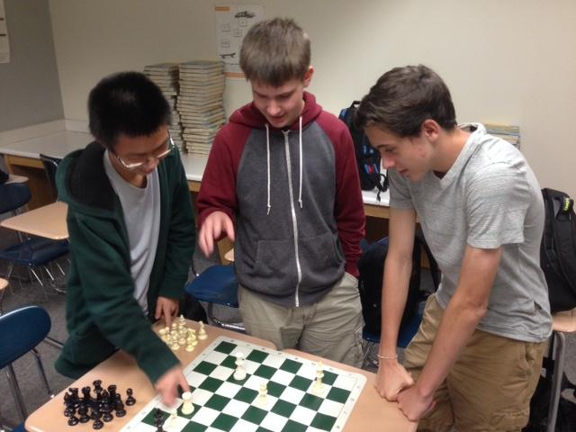 """Eric Zhu, Chess Club member and freshman, plays using the """"bughouse"""" against club members and sophomores Caleb Smith and Brett Khalow. According to Zhu, the """"bousehouse"""" is a partnered game where club members can learn from other members about tactics and playing speed."""