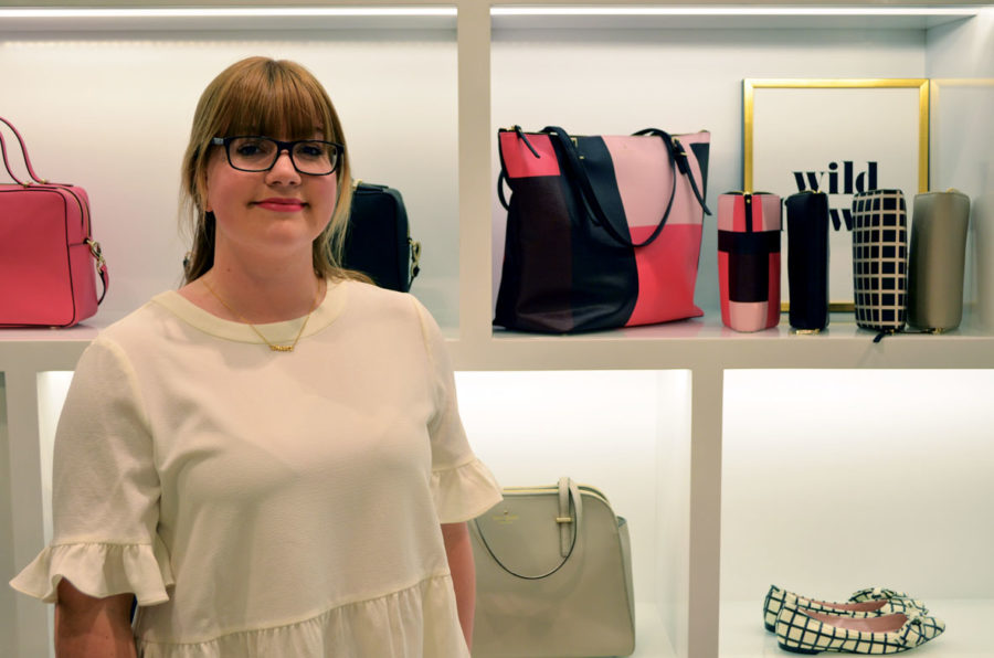 Wearing a Kate Spade top, senior Carley Lanham stands in front of a display in the Kate Spade at the Fashion Mall where she works. Lanham said she has seen more upperclassmen at CHS wearing affordable luxury pieces. MICHELLE DAI / PHOTO