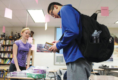 Junior Troy Li buys cookies from Girl Scout and junior Alex Isler. With the new Digital Cookie program, most Girl Scout troops are selling cookies online instead of in person. SWETHA NAKSHATRI / PHOTO